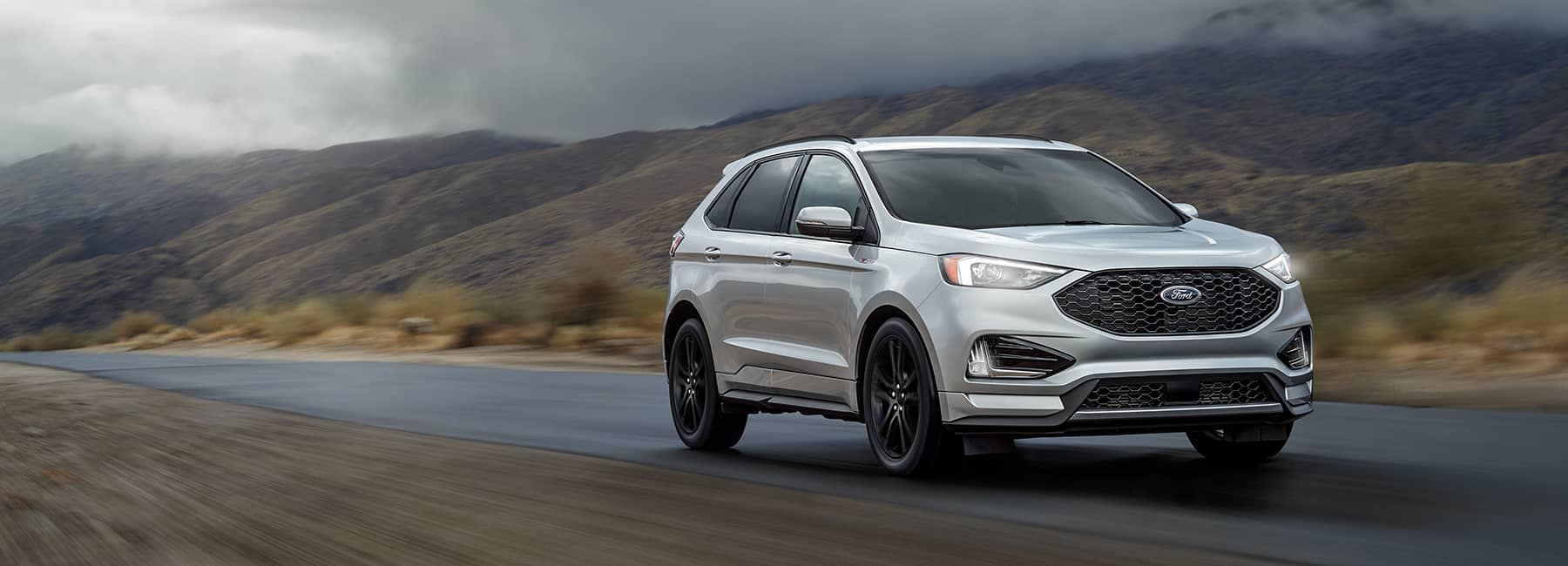 Silver 2021 Ford Edge driving along a foggy mountain pass