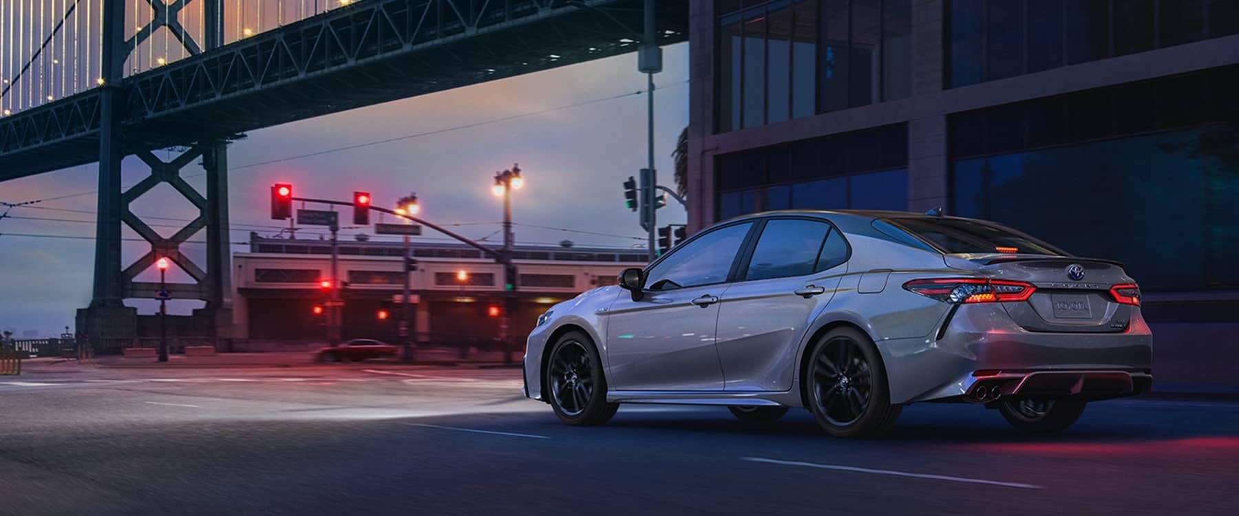 2021 Toyota Camry parked outside building by bridge