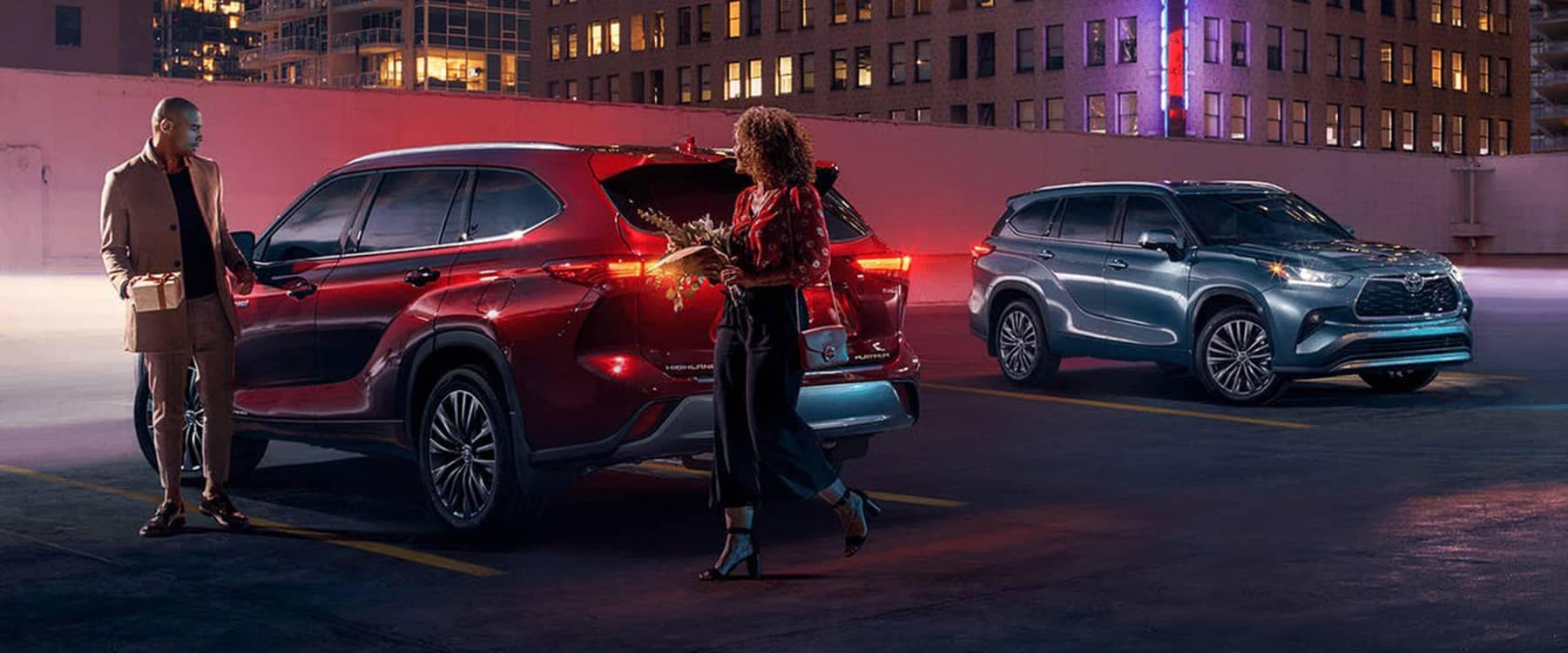 2021 Toyota Highlander Hybrid parked with two people with gifts