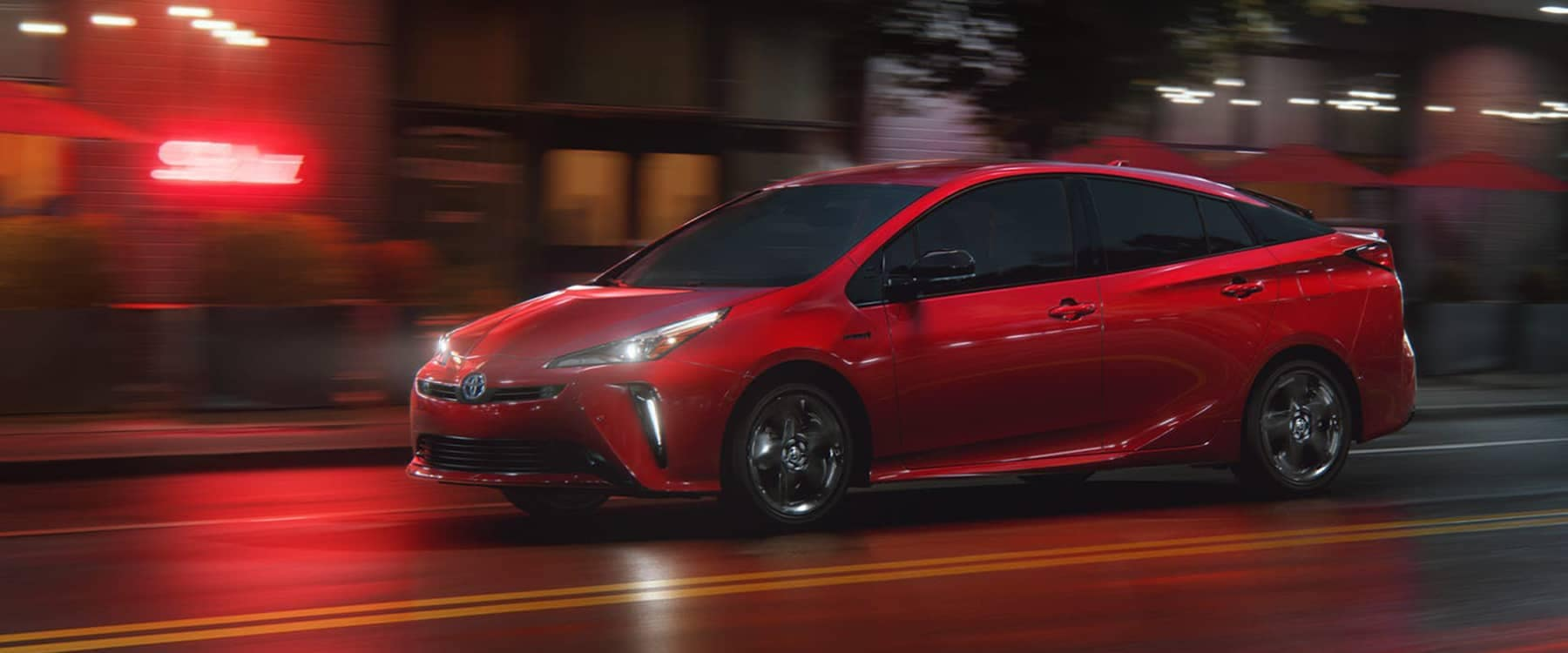 Red 2021 Toyota Prius driving down a road at night