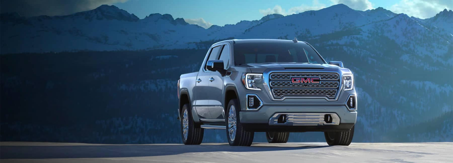 A silver GMC truck parked in front of a mountain range.