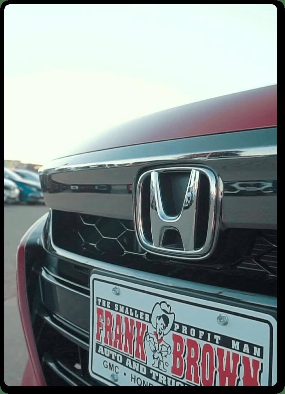Close up of Frank Brown Honda license plate on Honda car in car lot