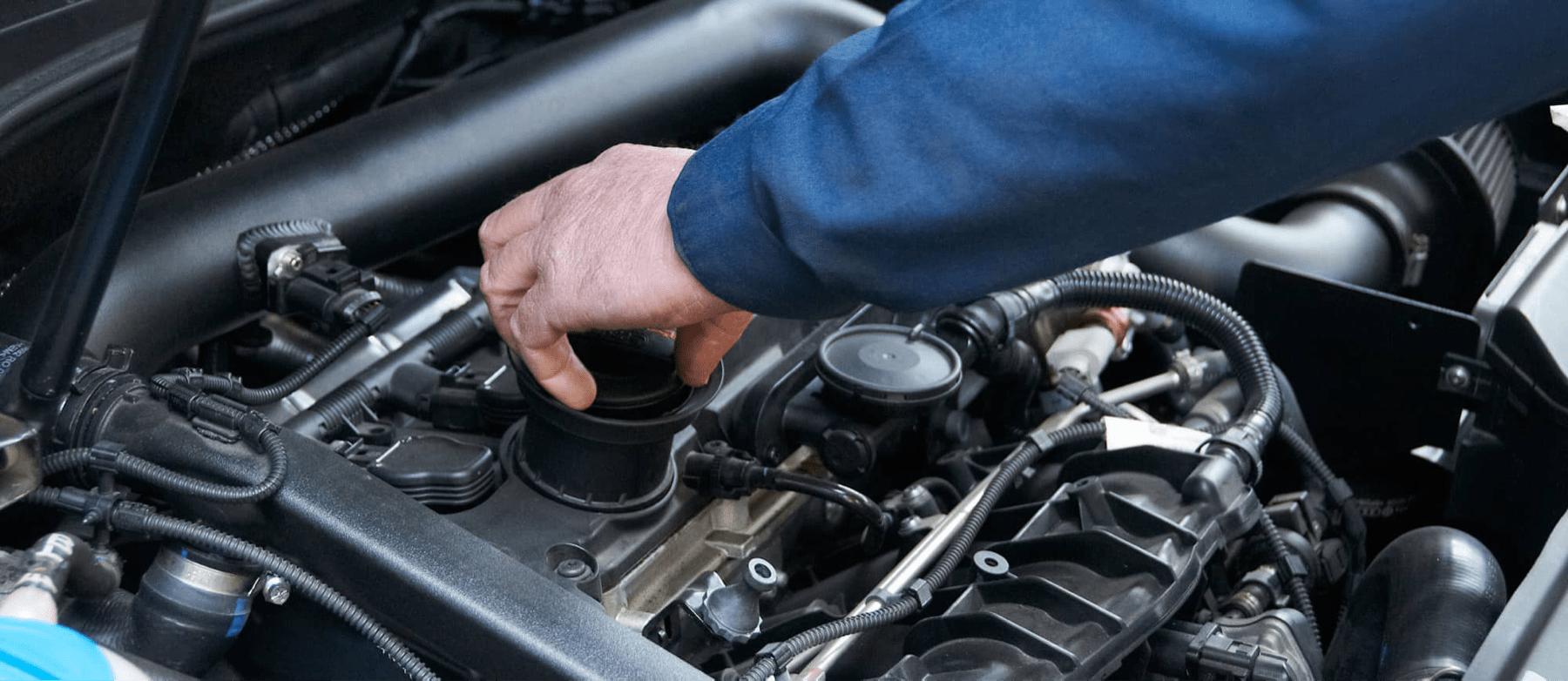 service technician unscrews oil reservoir in car engine