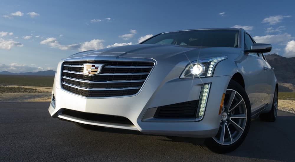 A used silver Cadillac on a test drive on a rural country road outside Fort Worth TX