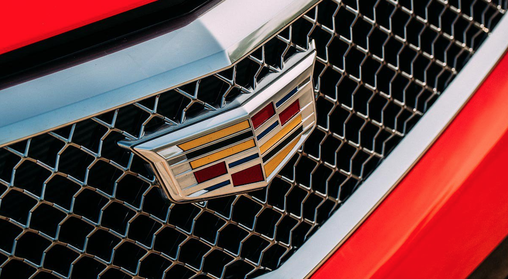 A closeup of the Cadillac logo on a red sedan