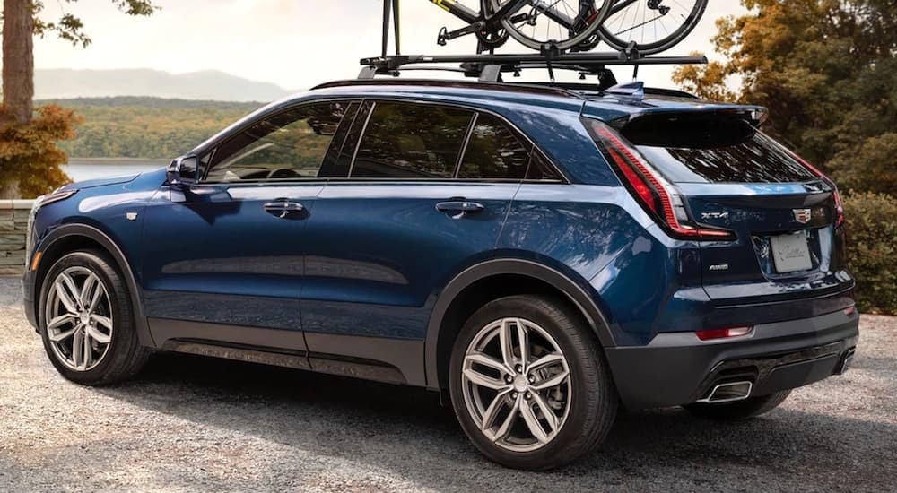 Dark blue 2019 Cadillac XT4 with bike on roof rack, parked in front of lake