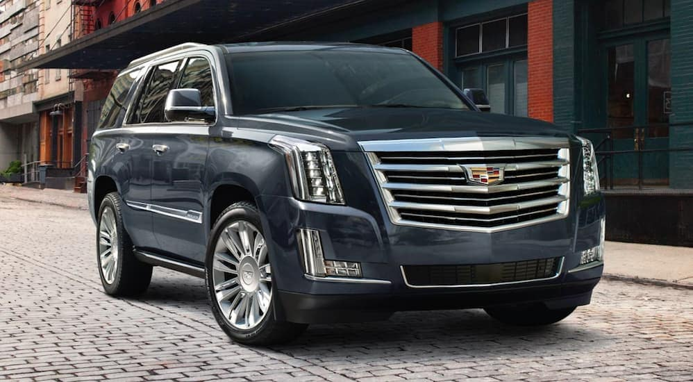 A dark gray 2019 Cadillac Escalade on a cobblestone city street