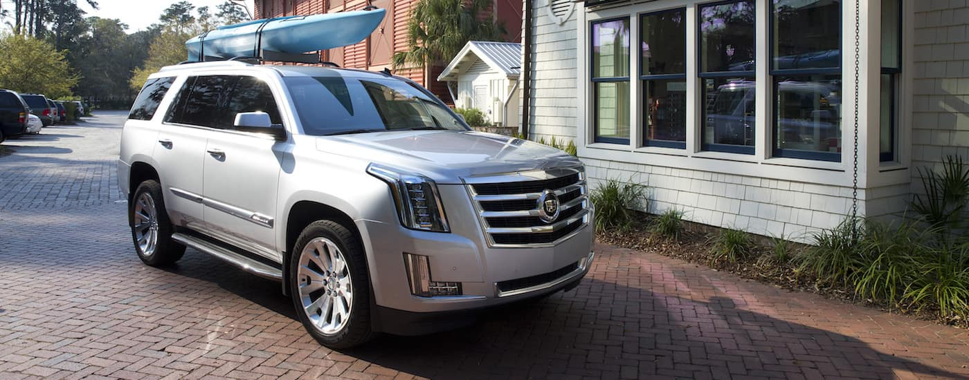 Used Cadillac SUV: A silver 2015 Cadillac Escalade with a kayak on the roof parked in a scenic town