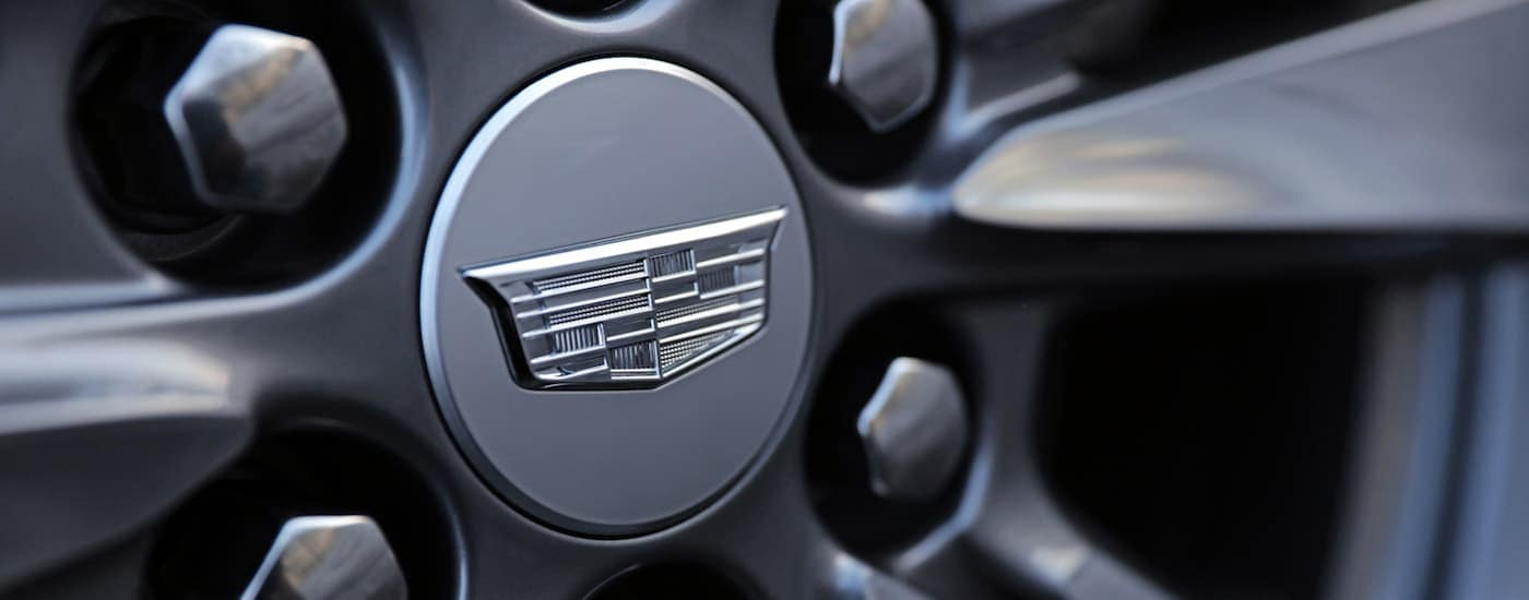 A closeup of the Cadillac logo on a gray Cadillac XTS wheel