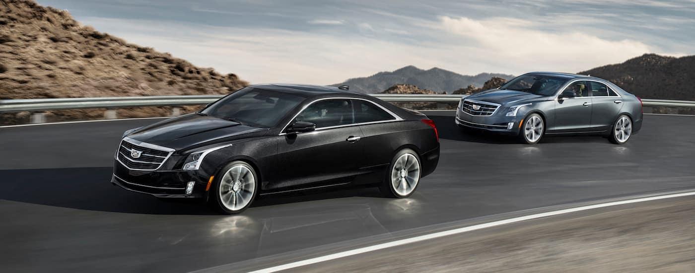 A black 2017 Cadillac ATS coup and silver ATS sedan racing along a mountain highway to a Cadillac dealer near me