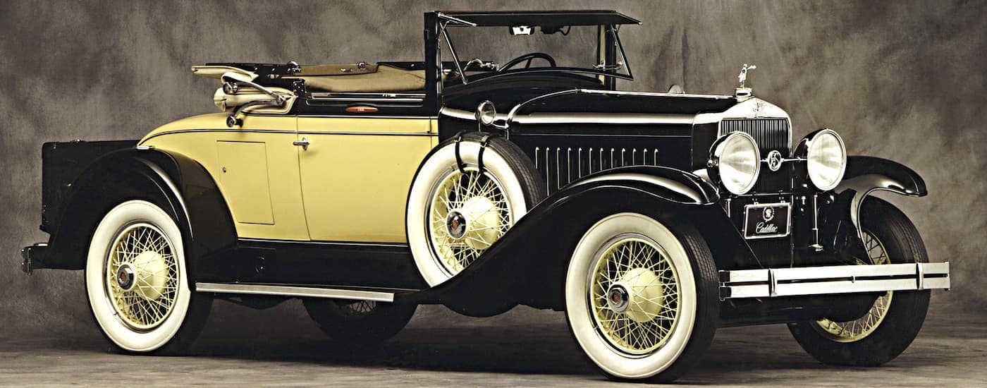 A yellow and black 1927 Cadillac LaSalle 303 Roadster on a gray background