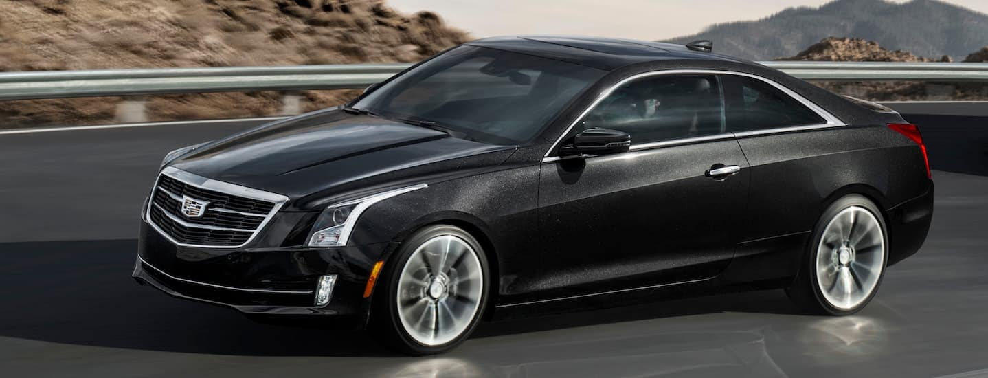 A black 2019 Cadillac ATS driving through mountains