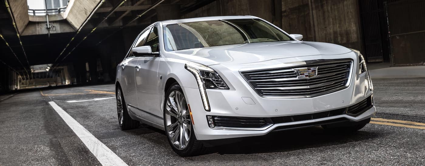 A silver 2017 Cadillac CT6, popular among used luxury cars, is driving under a highway bridge