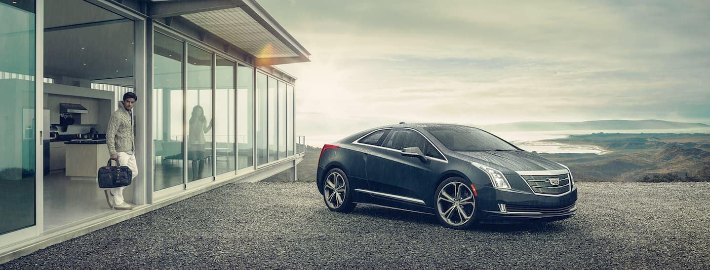 A used Cadillac ELR is parked in a driveway next to a house on a rainy day near Fort Worth, TX.