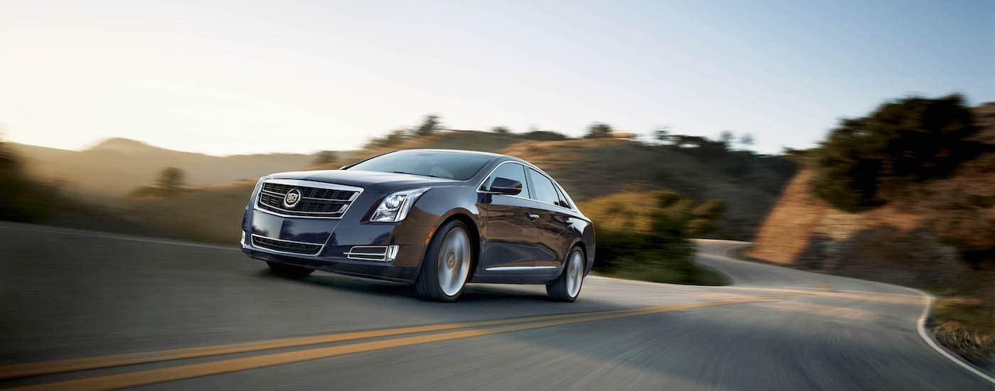 A grey 2015 Cadillac XTS, popular among used luxury cars in Fort Worth, TX, is driving on a sunny road.
