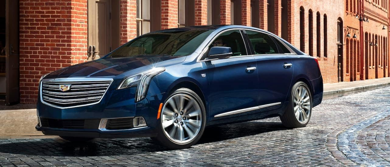 A used blue Cadillac XTS on a cobblestone road