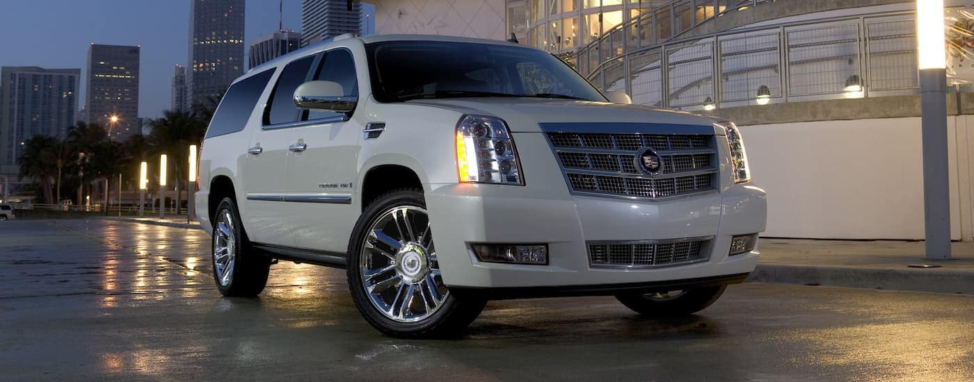 A white 2009 Cadillac Escalade, popular among used luxury SUVs for Fort Worth, TX drivers, is parked with a city behind it