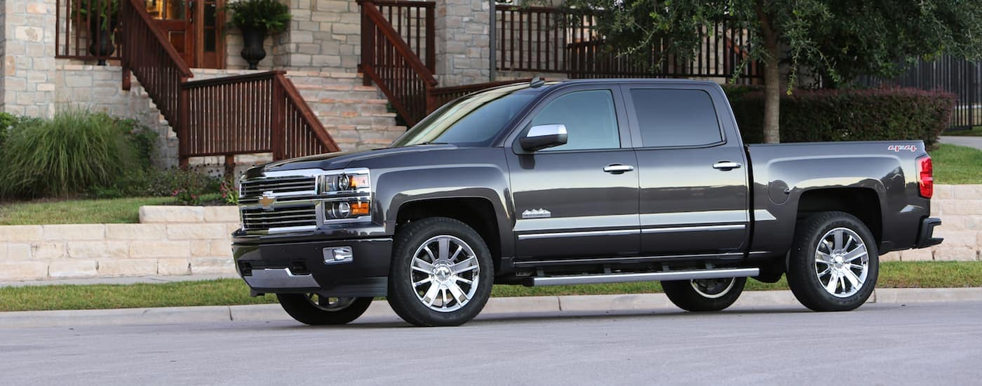 A gray 2014 Chevy Silverado for sale, parked outside an upscale home.