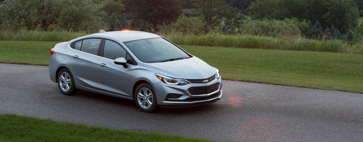 A silver 2017 Chevy Cruze, popular among Chevy used cars, is parked on a narrow paved road with sun flares.