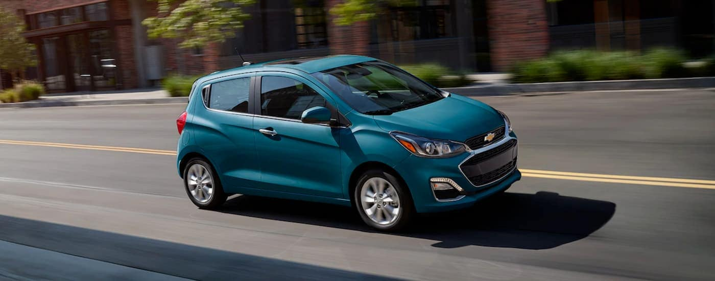 A blue 2019 Chevy Spark is driving downtown after leaving a Chevy dealership near Fort Worth, TX.