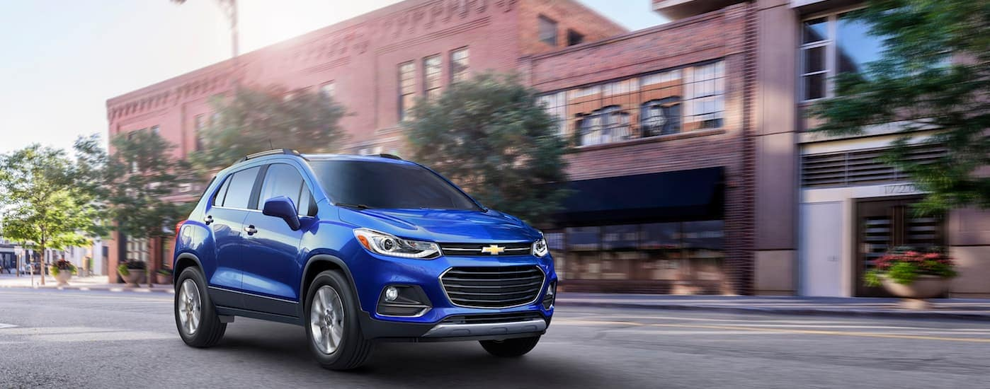 A blue 2017 Chevy Trax, popular among used cars in Fort Worth, is driving down a town street in Texas.