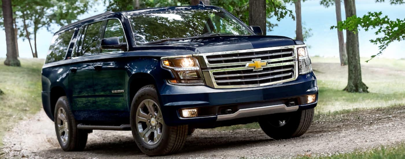 A blue 2019 Chevy Suburban is on a dirt road after leaving a Chevy dealership near Dallas.