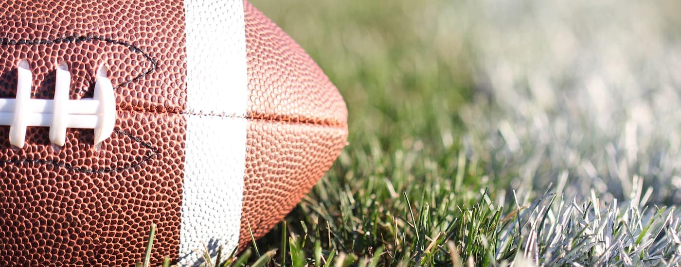 A football is shown in a closeup in a field. Catch a Cowboys game after visiting a Chevy dealership near Dallas.