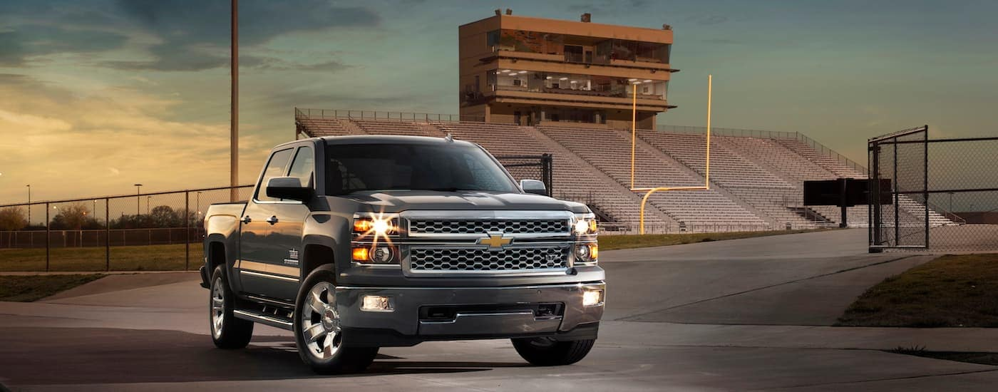 A grey Texas Edition 2015 Chevy Silverado, popular among used Chevy trucks, is parked in front of a football field at dusk.