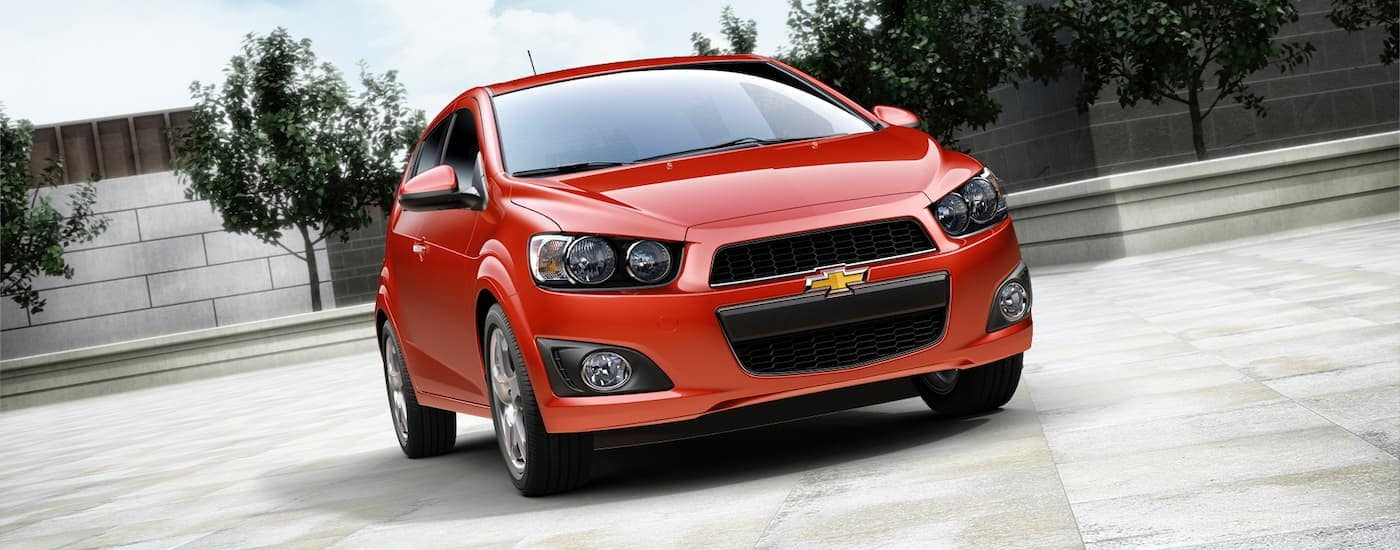 A red 2015 Chevy Sonic is parked in front of a fountain after leaving a used car dealership near me in Ennis, TX.