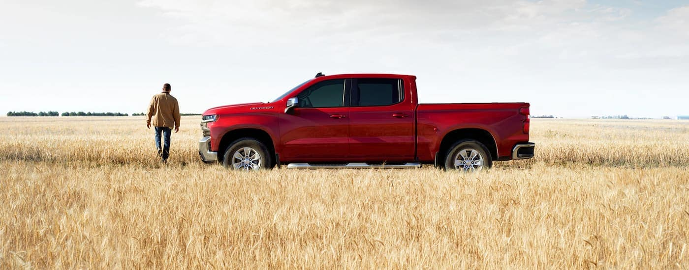 A man is in a field with his red 2020 Chevy Silverado after leaving the best Chevy dealer near Waxahachie, TX.