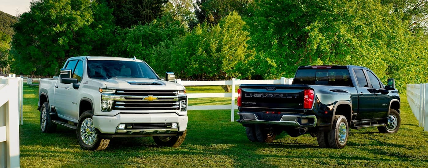 A white 2020 Chevy Silverado 2500HD is parked next to a black 3500HD, which came from a Chevy dealer near me near Arlington, TX.