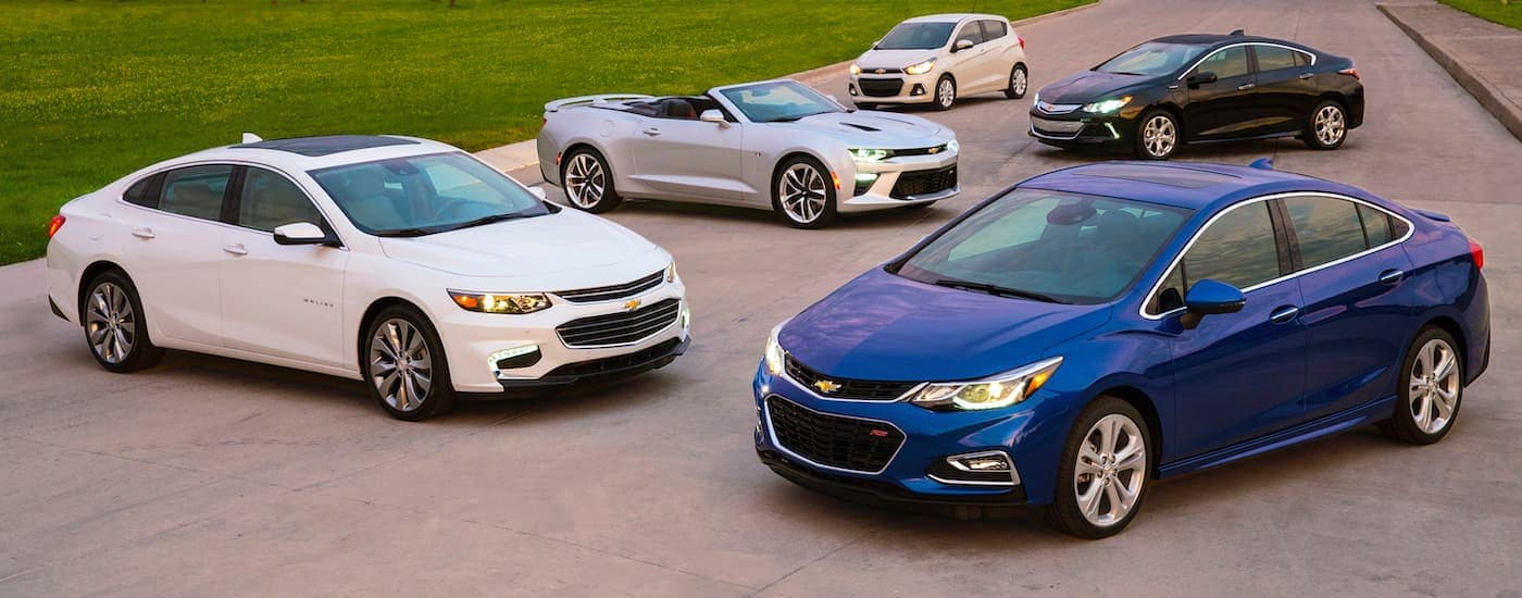 A 2016 Chevy Cruze and a 2015 Malibu, Camaro, Spark and Volt are all parked outside one of the best used car dealers in Ennis County, TX.