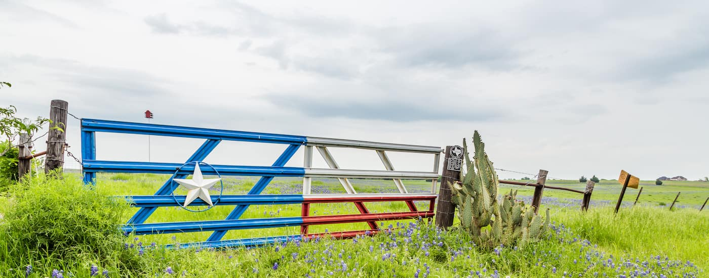 A Texas gate at a farm in Ennis, TX is shown, where a great local used car dealer is located.