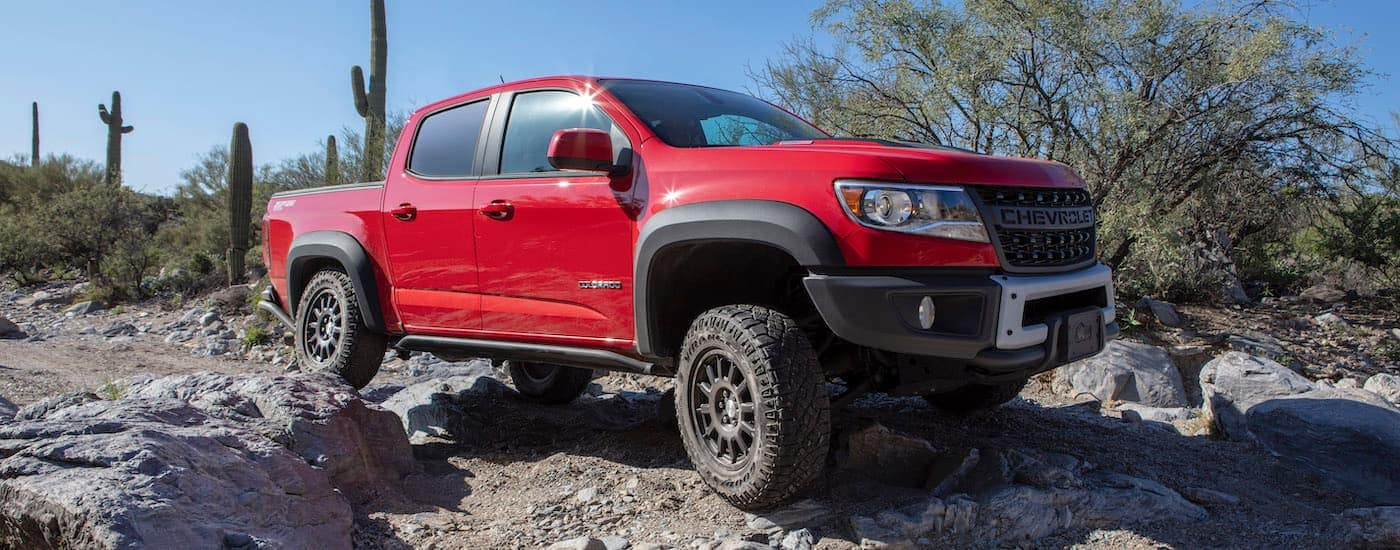A red 2020 Chevy Colorado ZR2 Bison, one of the exciting Chevy trucks, is off-roading on a trail outside of Ennis, TX.