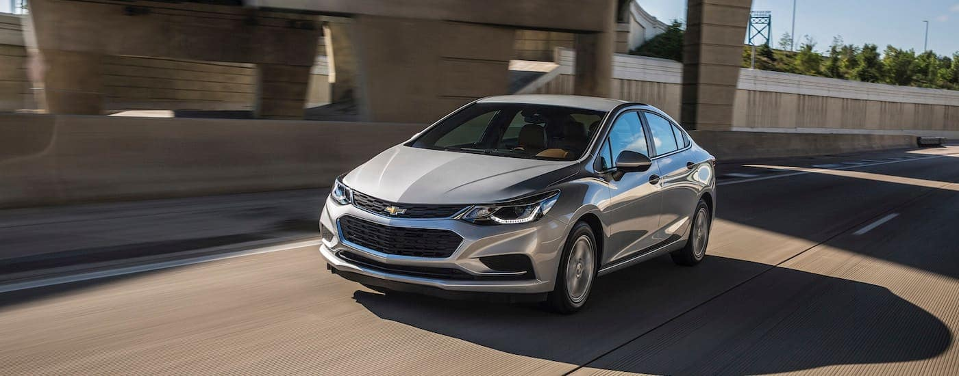 A silver Chevy Certified Pre Owned 2017 Cruze Diesel is driving on a highway near Ennis, TX.