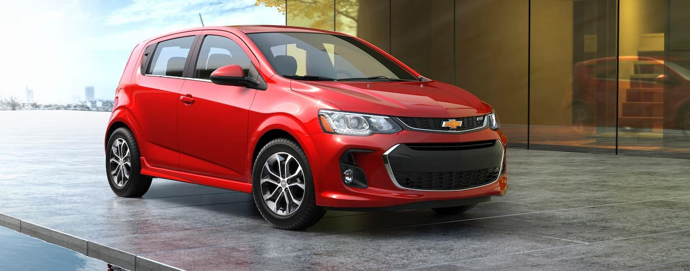 A red 2017 Chevy Certified Pre-owned Sonic is parked in front of large windows near Ennis, TX.