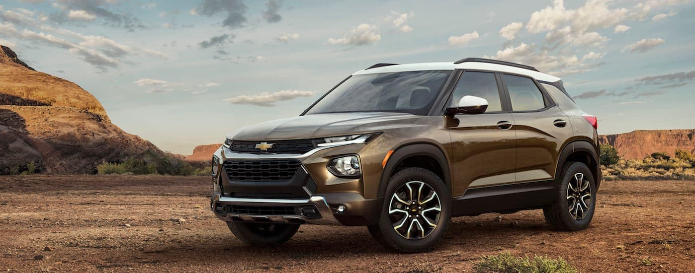 A brown 2021 Chevy Trailblazer, which will be an all-new model added to the Chevy SUVs, is parked in a desert area on a sunny day.