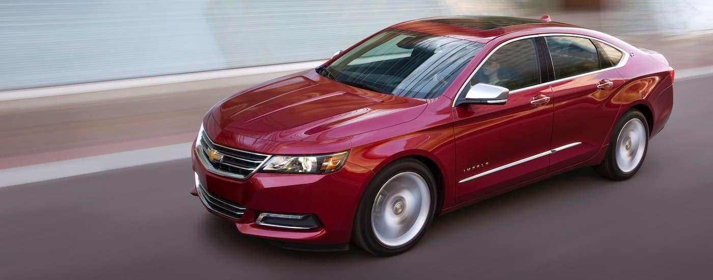 A red 2018 Chevy Impala, popular among used cars near me, is driving past a blurred white building in Waxahachie, TX.