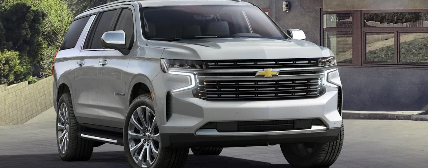A silver 2021 Chevy Suburban, which is soon to be a favorite among Chevy SUVs, is parked in front of an Ennis, TX, home.
