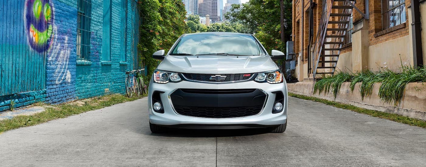 A popular vehicle at Chevy dealerships near Dallas, a silver 2020 Chevy Sonic RS is parked in an alley, shown from the front.
