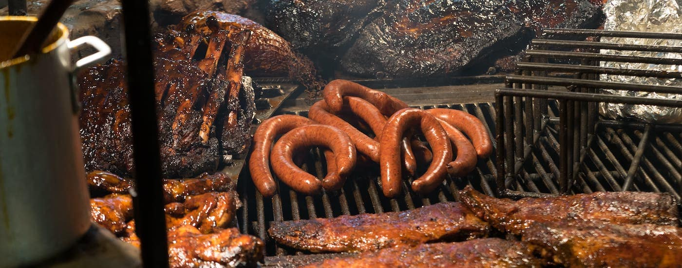 An assortment of different meats are shown on a grill at a barbeque around Waxahachie and Fort Worth, TX.