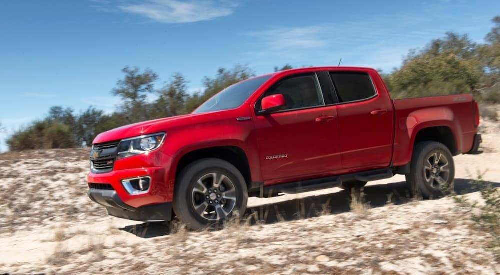 A red 2019 Chevy Colorado Diesel driving on dunes with trees in the background.