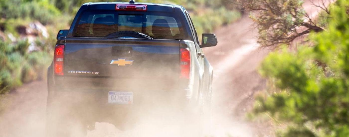 A black 2017 Chevy Colorado is driving down a dusty dirt road in Ennis, TX. Chevy Certified Pre Owned is a great way to get into a vehicle.