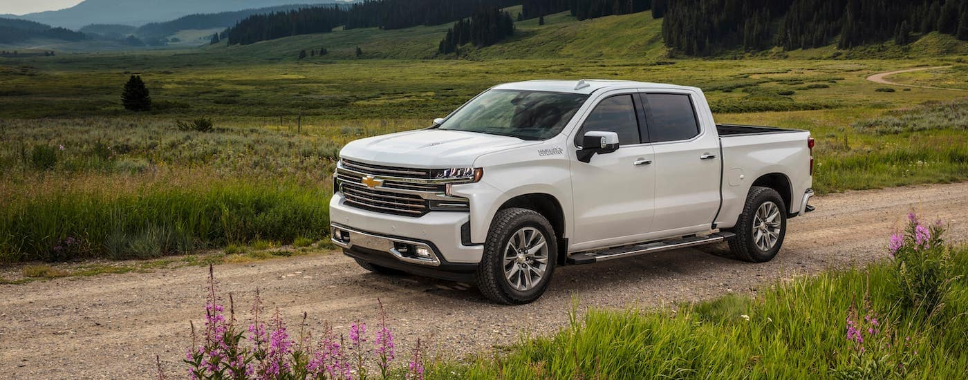 A white 2020 Chevy Silverado 1500 High Country from your local Chevy dealer near you is driving on a dirt road through a field outside Ennis, TX.