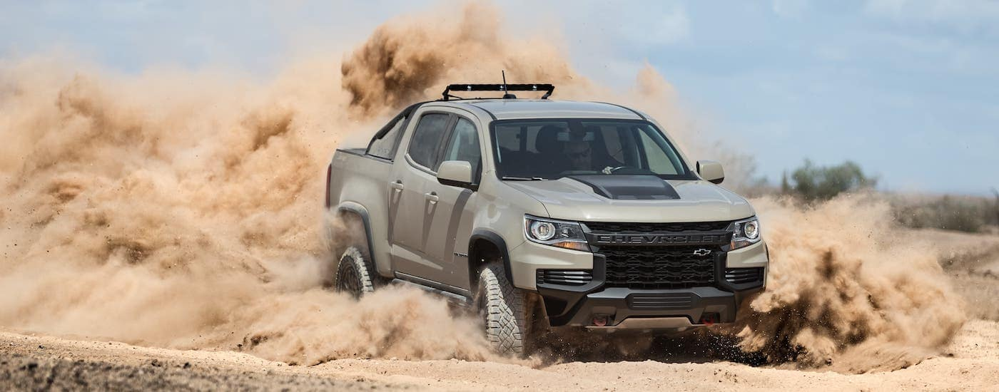 A tan 2021 Chevy Colorado ZR2, soon to be at a Chevy dealer near you, is kicking up sand on a trail near Ennis, TX.