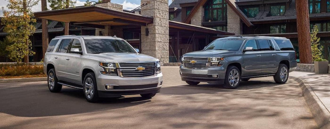 A silver 2020 Chevy Tahoe and a gray 2020 Chevy Suburban are parked in front of lodge outside of Ennis, TX.