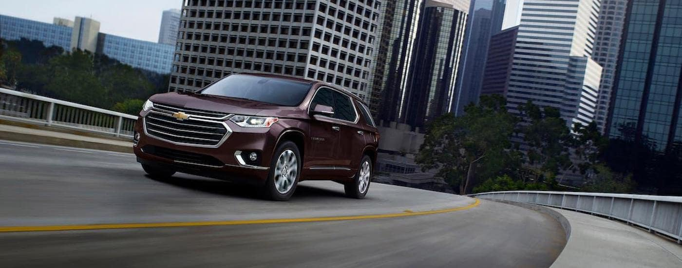 A maroon 2020 Chevy Traverse is driving away from a city outside Ennis, TX.
