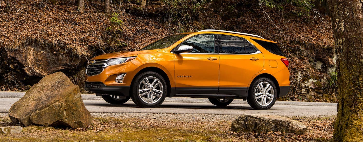 An orange 2020 Chevy Equinox is driving on a road past fall foliage.