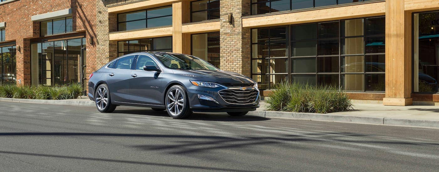 A gray 2020 Chevy Malibu is parked in front of a tan stone Chevy dealership.