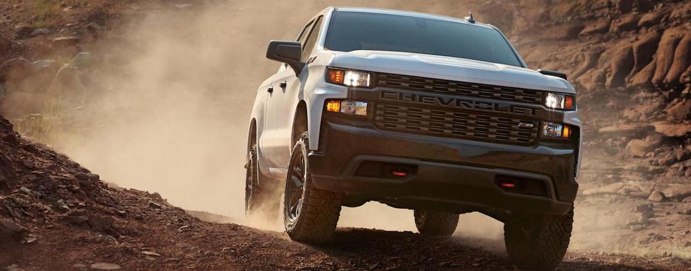A white 2020 Chevy Silverado 1500 is off-roading on a dirt trail.